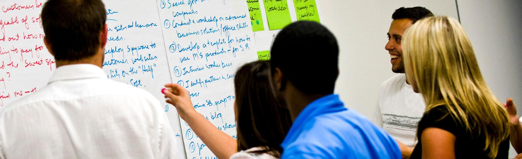 GSEP students write on the board - Pepperdine GSEP